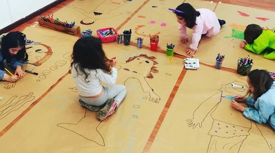 Niñas pintando sobre papel estraza