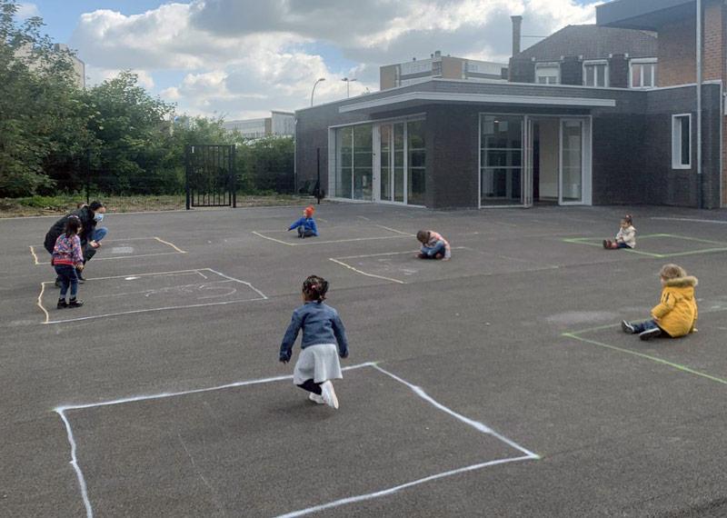 Niños pequeños en el patio de una escuela, separados por cuadrículas