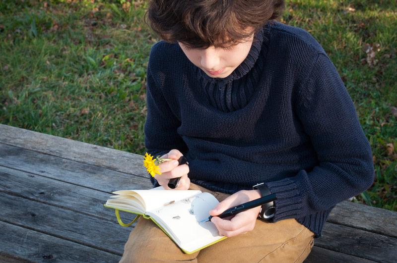 Niño copiando una flor en su cuaderno de campo