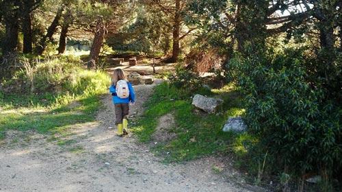Niña llegando por un camino a la escuela bosque
