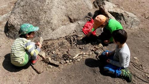 Niños jugando con ramas y piedras