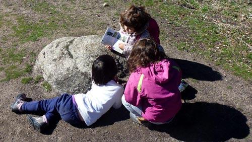 Una niña muestra a otras un libro
