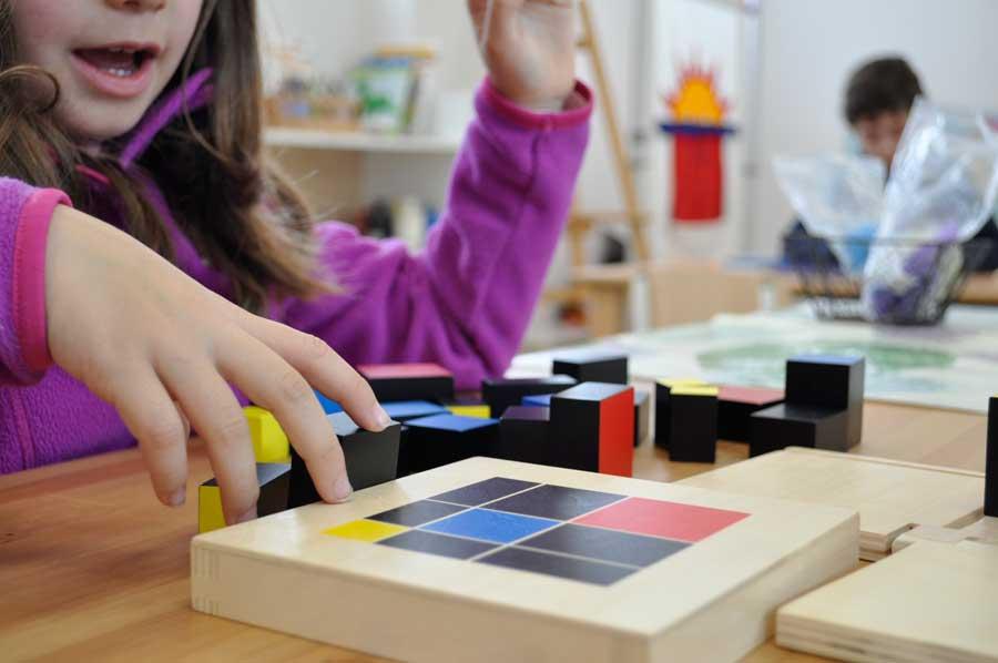 Niña trabajando con materiales manipulativos Montessori